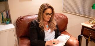 A psicóloga Simone Caon aparece sentada em poltrona no seu consultório lendo um livro